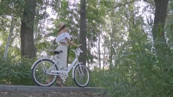 Fotoaparátu na štíhlá brunetka v bílé sukni, blůzu a doškové klobouk, který stojí uprostřed parku s městské kolo a hledá pro někoho mezi lidmi a pak se otočí