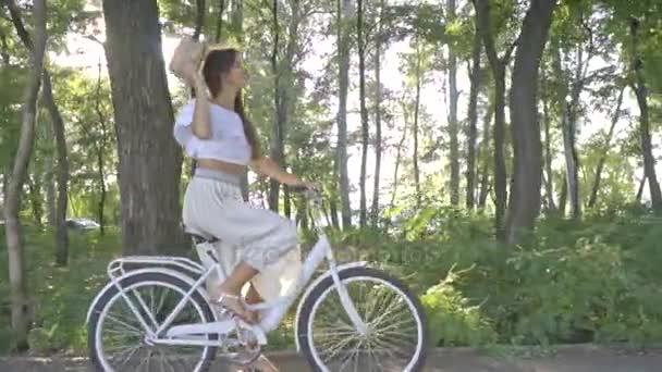 Brunetka v bílé sukni, halenku, jízda na slunci na městské kolo podél cesty v parku a slaměný klobouk, opouští rám. Zpomalený pohyb, Střelba