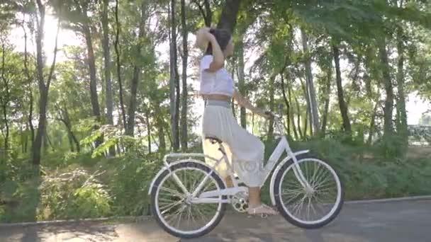 Bruneta v bílé sukni, halenku je jízda na slunci na kole bílé města podél cesty v parku, sundá jí slaměný klobouk a třese její vlasy, Zpomalený pohyb, Střelba