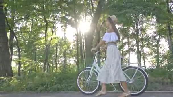 Pěkná brunetka v bílé sukni, halenku válí v paprscích slunce město kolo na cestě v parku a rozhlížel se kolem, Zpomalený pohyb, Střelba
