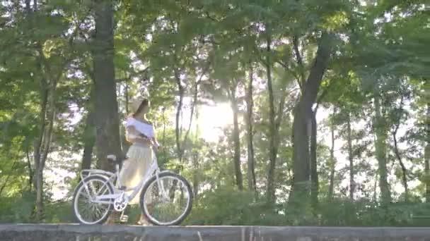 Sladká bruneta v bílé sukni, halenku je válcování na slunci bílé městské kolo podél cesty v parku a rozhlížel se těší krásné letní počasí pod širým nebem, pomalý