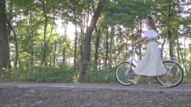 Szép lány egy fehér szoknya, blúz, gurul a sunshine city bike azon az úton, a parkban, élvezi egy napsütéses napon, lassú mozgás, lövés