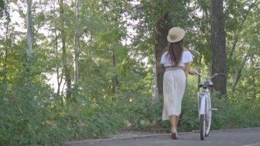 Barna-fehér szoknya, blúz és szalma kalap, egy parkban, egy napsütéses délutánon város kerékpár tartó, nevetve nézett vissza és integetett a szoknyája