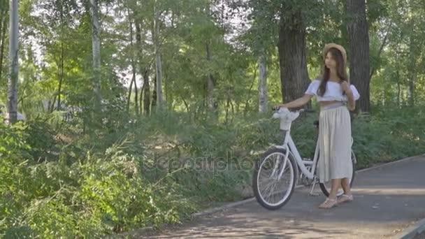 Sladká brunetka v bílých šatech a v klobouku s tetování upraví vlasy a drží městské kolo, Zpomalený pohyb, Střelba