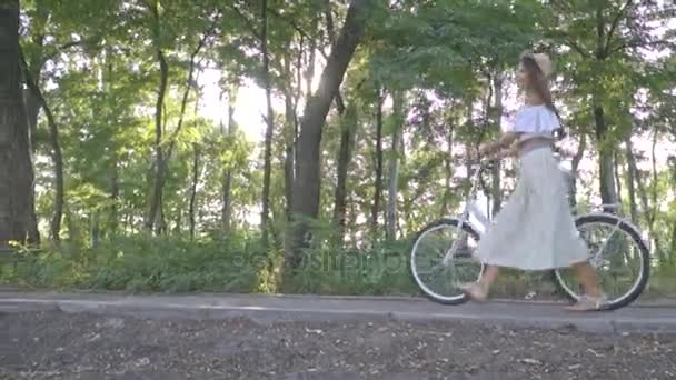 Krásná dívka v bílé sukni, blůzu válí v sluníčko městské kolo na cestě v parku těší slunečný den, Zpomalený pohyb, Střelba