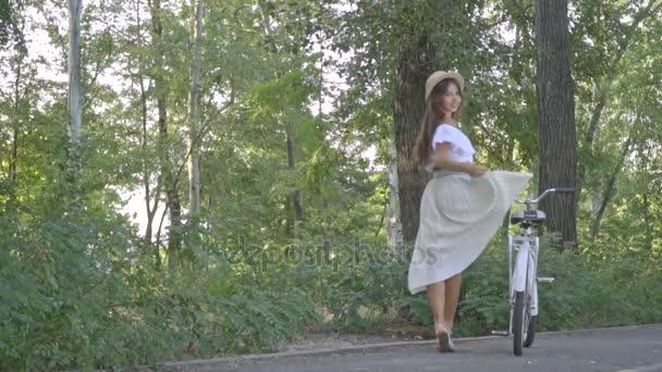 Šťastný, bruneta s dlouhými vlasy v bílé sukni, blůzu a slaměný klobouk v parku na Slunečné odpoledne drží město kolo, se ohlíží zpět a odešle vzduchu polibek, Zpomalený pohyb, Střelba