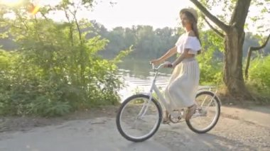 Egy aranyos barna hosszú szoknya, fehér blúz és integetett egy szalmakalapot lovagol az úton, a folyó egy fehér city kerékpár