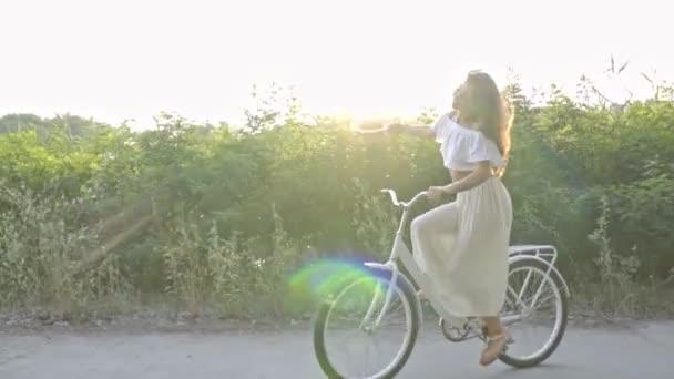 Veselá brunetka žena mává slaměný klobouk jíst na městské kolo podél staré silnice v letním dni