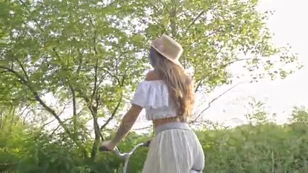 Půvabná brunetka mává slaměný klobouk, jezdit na kole město na starou silnici v létě, zadní pohled