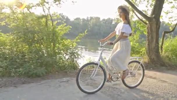 Roztomilá brunetka v dlouhé sukni, bílou halenku a mávat slaměný klobouk jízdy na silnici řekou na bílém městské kolo