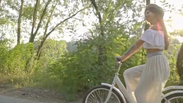 Romantický bruneta v sukni, bílou halenku a slaměný klobouk jezdí na silnici vedle řeky na bílé město kolo a vesele usmívá, pomalý