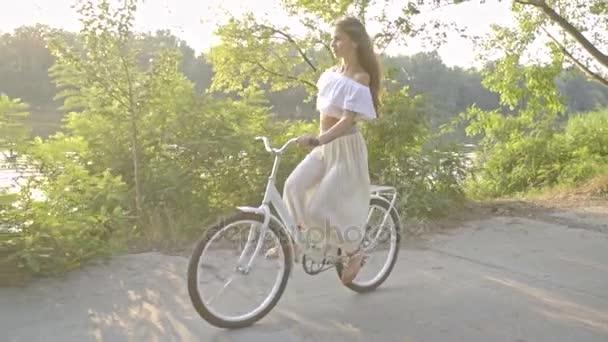 Brunetka jezdí městské kolo na slunné odpoledne, zpomalené střílení