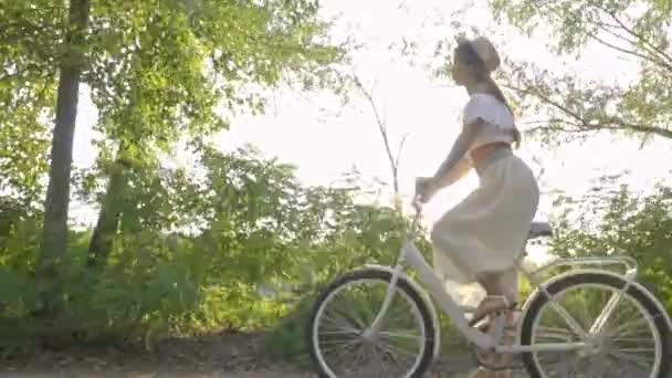 Brunetka v slamák jezdí městské kolo za slunečného dne, boční pohled