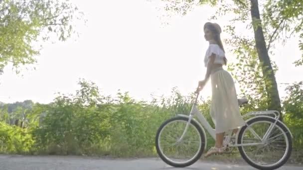 Brunetka ve slamáku jezdí městské kolo v slunci na přírodu, Zpomalený pohyb, Střelba
