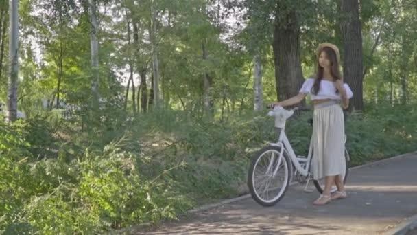 Bruneta s zamyšlený pohled v slaměný klobouk, dlouhé sukně a Bílé halenky stojí městské kolo v parku