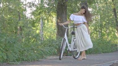 Egy vidám barna hosszú hajú, fehér szoknya, a blúz-e a parkban a napsütéses délután tart egy city kerékpár- és ugráló örömében valamiben, lassú mozgás