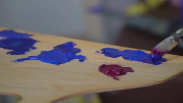 The painter slowly mixes a blue paint brush on a wooden palette
