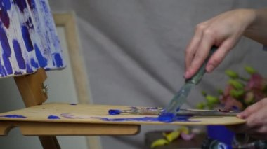 The girl takes blue oil paint from the palette and spreads it on the canvas with a spatula