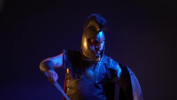 Gladiatore romano con la barba lunga con una cicatrice sul suo volto in un casco e armatura copre la testa con uno scudo e onde la sua spada nella priorità bassa scura, rallentatore riprese