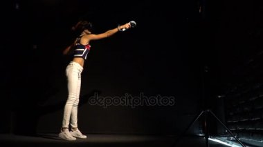 A girl with virtual reality glasses and two joysticks in her hands plays a game in a dark room