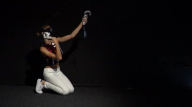 A girl in virtual reality glasses rejoices in victory and rises from her knees in a dark room