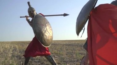 The Roman warrior attacks with a spear and repels the opponent with a shield with his foot, slow motion