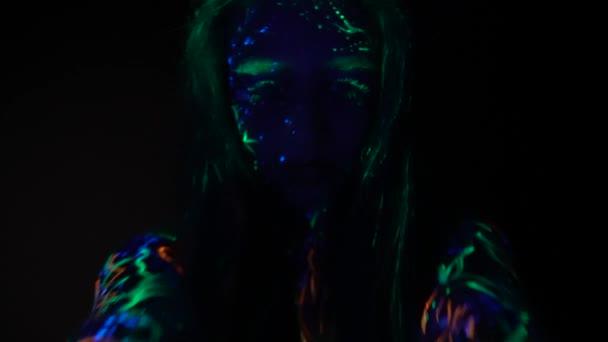 Fotoaparát v rukou dívky se blíží tvář maloval fluorescenční barvou