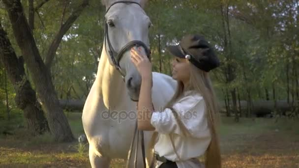 Dlouhé vlasy-jezdkyně v lese, v pozadí běží pes Husky