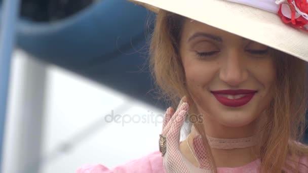 Žena v bílém klobouku roztomilý, s úsměvem a při pohledu na fotoaparát stojící na letadlo pozadí, zpomalené