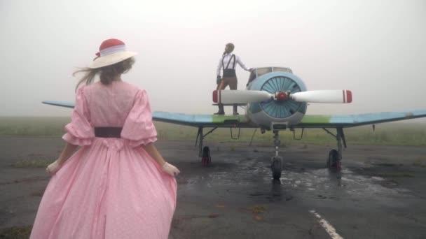 Zpomalené střílení jako žena v růžových šatech se blíží muž v obleku piloti 60s, který stojí na vinobraní letadlo a dívá do dálky
