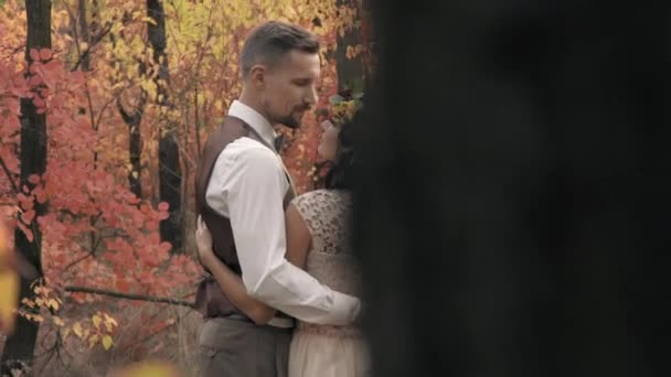 Among the trees in the autumn forest is an embrace of a couple in love