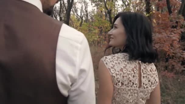 A dark-haired woman in a lace dress walks through the park with a man and looks back at him with a smile, slow motion