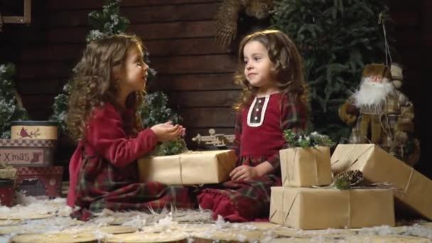 Decorazioni Sala Capodanno : Due bambine sedersi tra i doni nella sala con decorazioni