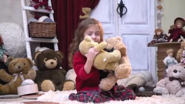 Malá holčička v šatech objetí s medvídky v místnosti s hračkami, pomalý pohyb