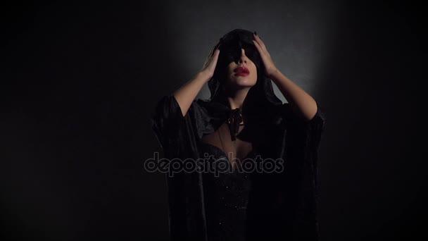 Sexy Hexe in schwarz drückt auf den Kopf eine Haube aus dem Mantel, Slow-motion