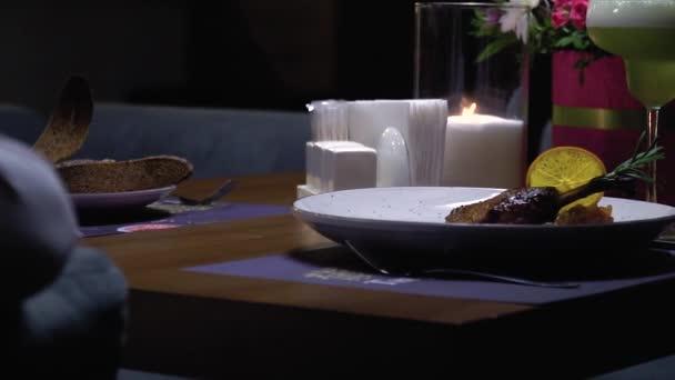 Romantický stůl se svíčkami, na kterém je masový pokrm s citronem