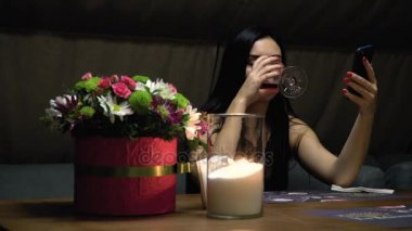A girl looks into a smartphone and drinks a red wine