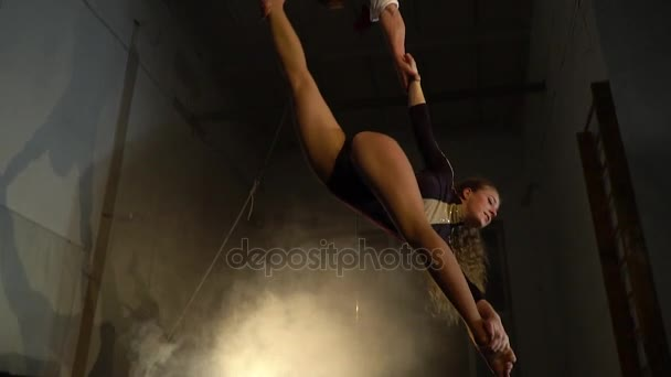 The blonde does twine in the air while the man holds her