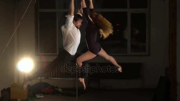 Beautiful pair of aerialists in the light of a lamp whirling in the air, slow motion shooting