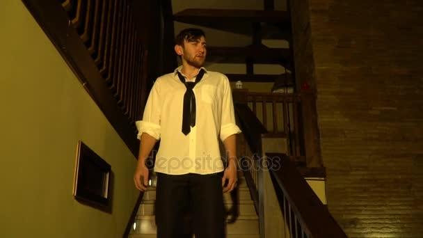 Ospalý muž v obleku sestupuje po schodech, pomalý pohyb