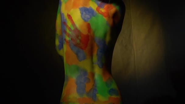A small woman in a multi-colored body art looks back and covers her breast with her hand