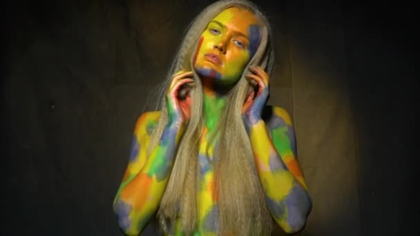 Mysterious girl in body art poses on camera adjusting hairstyle