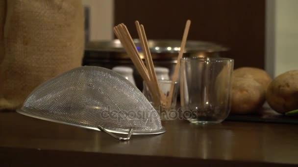 Kuchyňský stůl, na kterém leží brambor, paprika, sítem a brýle s dřevěnými holemi a koření
