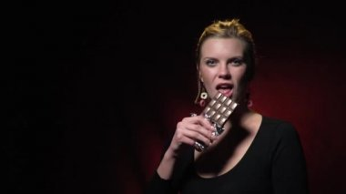 A blonde in a black sweatshirt stands on a dark red background and bites off a piece of chocolate