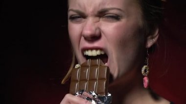 Beautiful blonde tears off a chocolate bar, slow motion