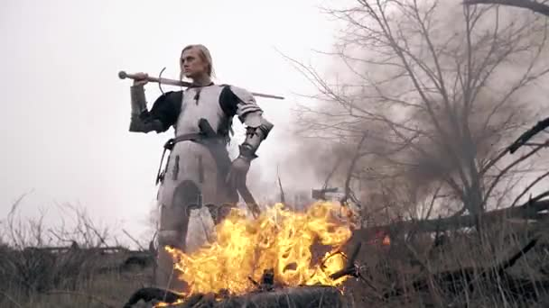Brutal Jeanne dArc stands by the fire and swings the sword