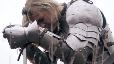 Jeanne D Arc bends over the sword and cries