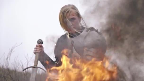 A brutal woman knight in armor leans against a sword sitting by the fire and looks into the distance, slow motion