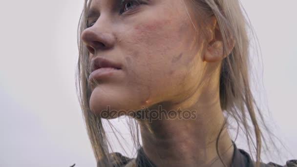 Jeanne Dark in the armor looks away, a tear runs down her cheek