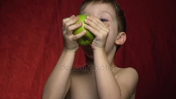 The boy is holding a big green apple and biting off a banana